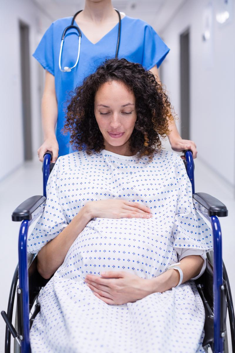 Une femme en fauteuil roulant est conduite en salle d'accouchement ©AdobeStock_135756327