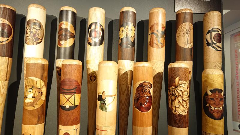Battes de baseball réalisées par des élèves en marqueterie exposées au musée du bois à Revel