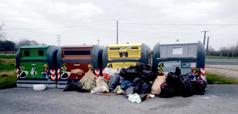 Sacs poubelle entassés devant des containers de collecte au bord de la D6089 entre Ménesplet et Montpon le 22 février 2021